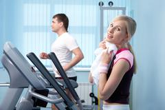 A young woman drying sweat with a towel in gym Stock Photos