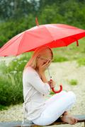 Portrait of sad young girl sitting on bench with umbrella Stock Photos