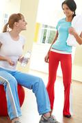 photo of two girls communicating in the gym on the background of mirrors - stock photo