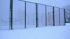 High metal outdoor tennis court fence covered dense snow winter Stock Footage