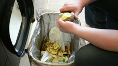 Man hands peel potatoes. paring fall into waste bin Stock Footage