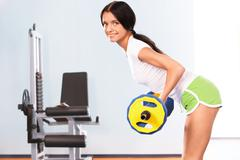 Stock Photo of photo of active girl standing on the floor and lifting dumbbell in the sports cl