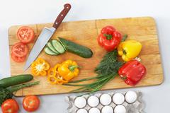 Still life of vegetables and kitchen-knife on cutting board Stock Photos