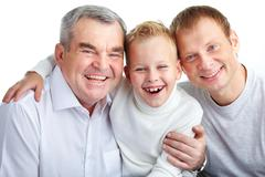 Portrait of joyful father, grandfather and son looking at camera Stock Photos