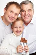 portrait of a father, grandfather and son with chocolate looking at camera with - stock photo