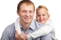 portrait of happy father and son looking at camera - stock photo
