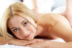 Portrait of calm female looking at camera during procedure of massage Stock Photos