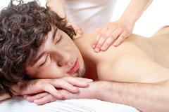Portrait of calm guy enjoying the procedure of massage Stock Photos