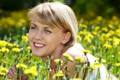 Portrait of charming girl with dandelion in green grass Stock Photos