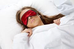 portrait of a young girl with eye mask sleeping under blanket - stock photo
