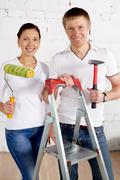 Industrious couple with paint roll and hammer looking at camera in new house Stock Photos