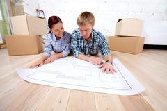young couple lying on the floor and looking at blueprint of new house - stock photo