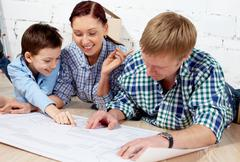 Young family discussing plan of new apartment Stock Photos