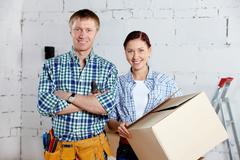 Happy couple looking at camera in new house Stock Photos