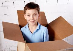 portrait of happy kid in box looking at camera - stock photo