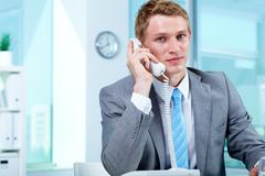 portrait of a businessman talking on phone in office - stock photo