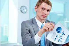 portrait of a serious manager holding document - stock photo