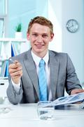 portrait of a successful employer with document looking and pointing at camera - stock photo