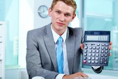 portrait of a successful employer with calculator looking at camera - stock photo