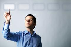 Image of young businessman pointing at virtual button Stock Photos