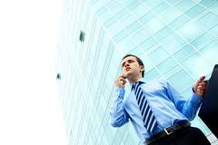 businessman standing by office building - stock photo