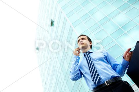 Stock photo of businessman standing by office building