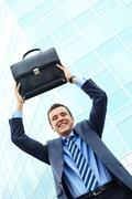 portrait of young businessman with briefcase looking at camera and smiling - stock photo