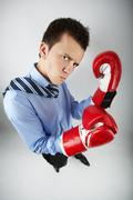 fisheye of angry businessman in boxing gloves posing in front of camera - stock photo