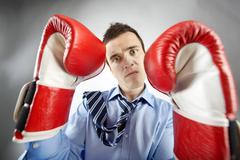portrait of businessman in boxing gloves posing in front of camera - stock photo