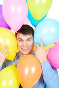 image of successful businessman face surrounded by multicolored balloons - stock photo