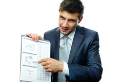Portrait of businessman pointing at diagram on paper Stock Photos