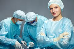 A young female surgeon against her two male colleagues Stock Photos