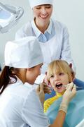Stock Photo of image of little girl having teeth checked by doctor and assistant