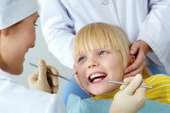 Stock Photo of image of little girl having her teeth checked by doctor and assistant