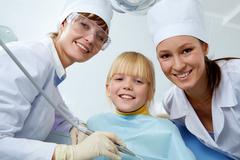 Group of dentist, assistant and little girl looking at camera Stock Photos