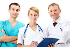portrait of friendly therapists standing in line and looking at camera with smil - stock photo