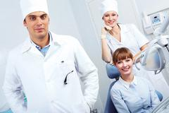 portrait of pretty woman and dentist with assistant behind - stock photo