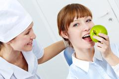 portrait of pretty woman eating a green apple with nurse near by - stock photo