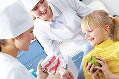 Image of dentist showing care dental hygiene to little girl with assistant near Stock Photos
