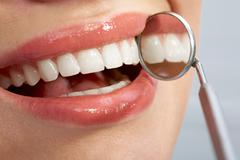Close-up of patient's healthy smile with mirror near by Stock Photos