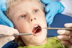 photo of little boy having mouth checkup in dental clinic - stock photo
