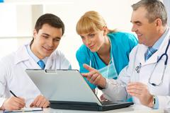 photo of aged physician pointing at laptop display while explaining something to - stock photo
