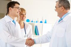photo of aged physician and young clinician handshaking with friendly nurse near - stock photo