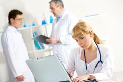 Photo of serious nurse with laptop planning work in working environment Stock Photos