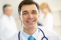 Portrait of cheerful doctor with stethoscope looking at camera and smiling Stock Photos