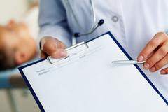 Hand of female doctor with pen pointing at clipboard Stock Photos