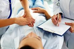 Close-up of two doctors during medical treatment of patient in hospital Stock Photos