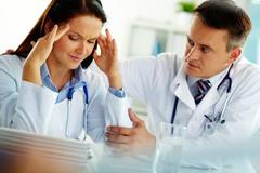 portrait of woman with headache touching her temples with colleague near by - stock photo