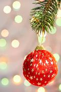 red christmas bauble with golden stars hanging on coniferous branch - stock photo