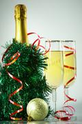 Two champagne flutes with green tinsel, bottle of champagne and toy ball near by Stock Photos